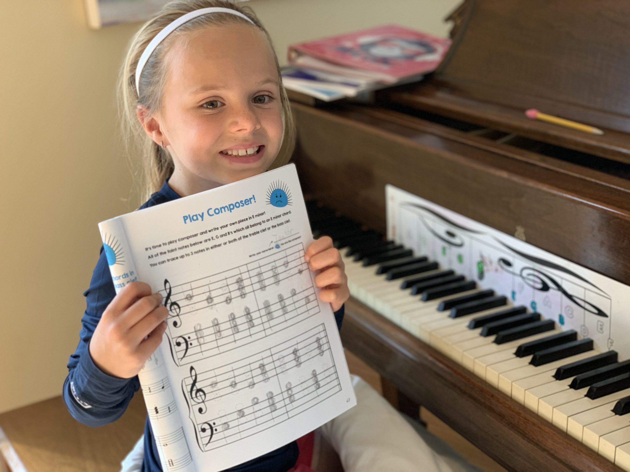 Piano student showing off her completed composer page in the Cascade Method Chords 1 Book