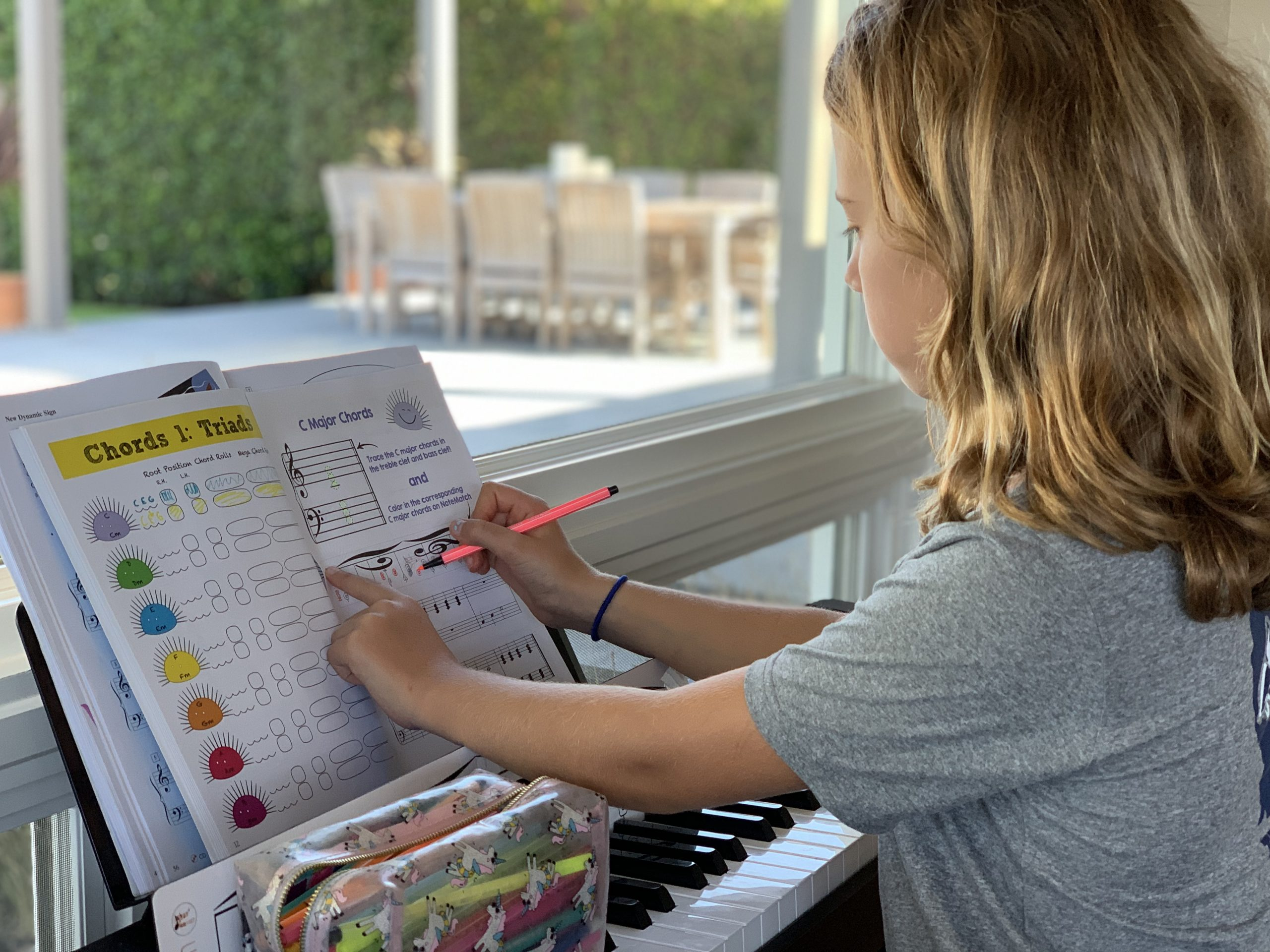 Student drawing in the chords on her mini notematch within the chords 1 book