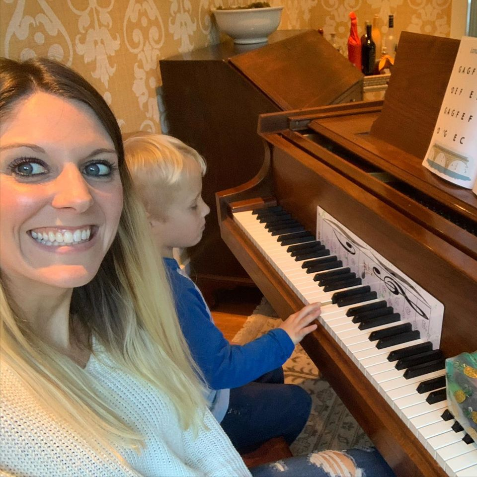 Tara smiling with her student while he plays the piano