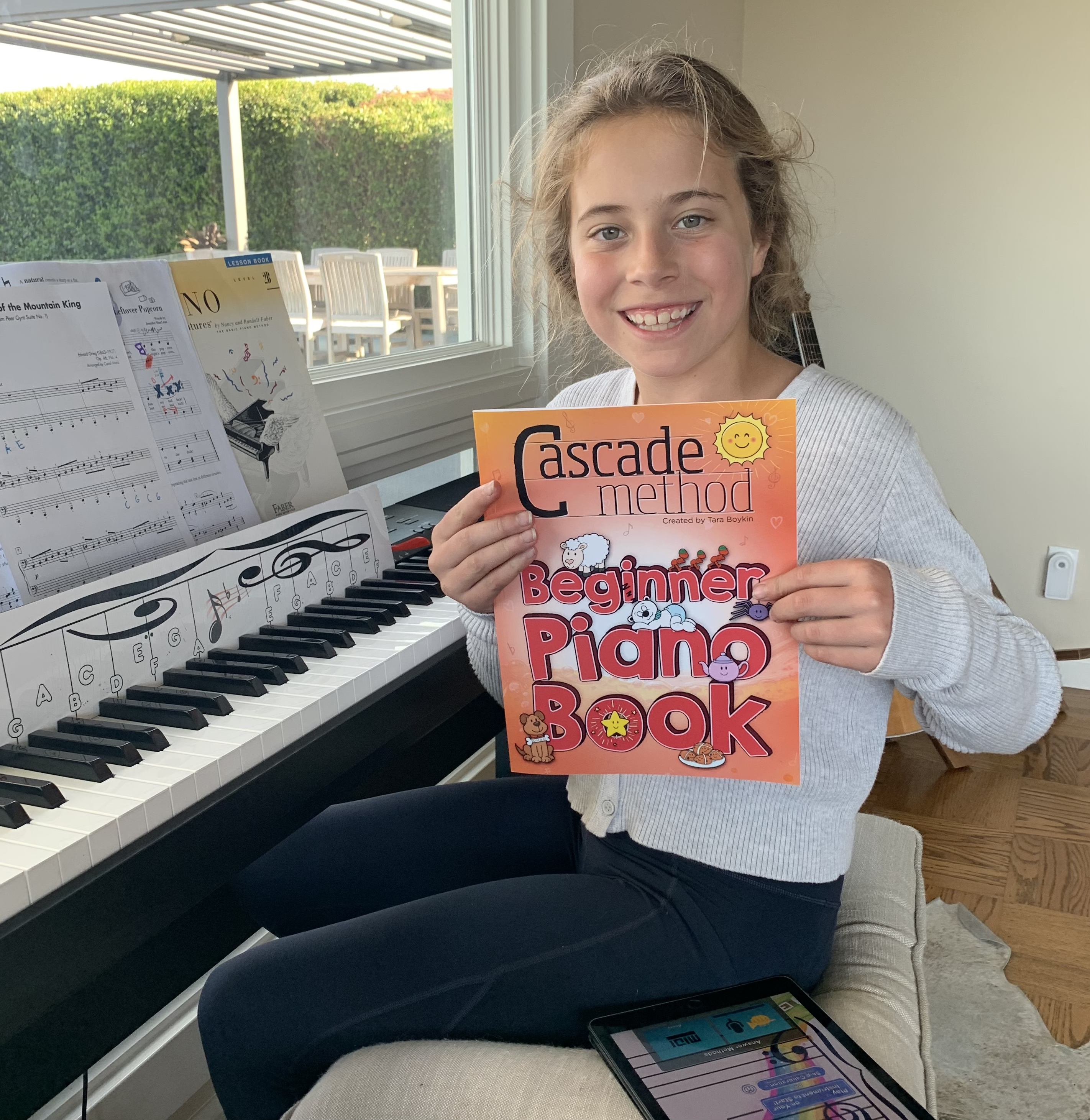 Girl student holding up the Beginner Piano Book