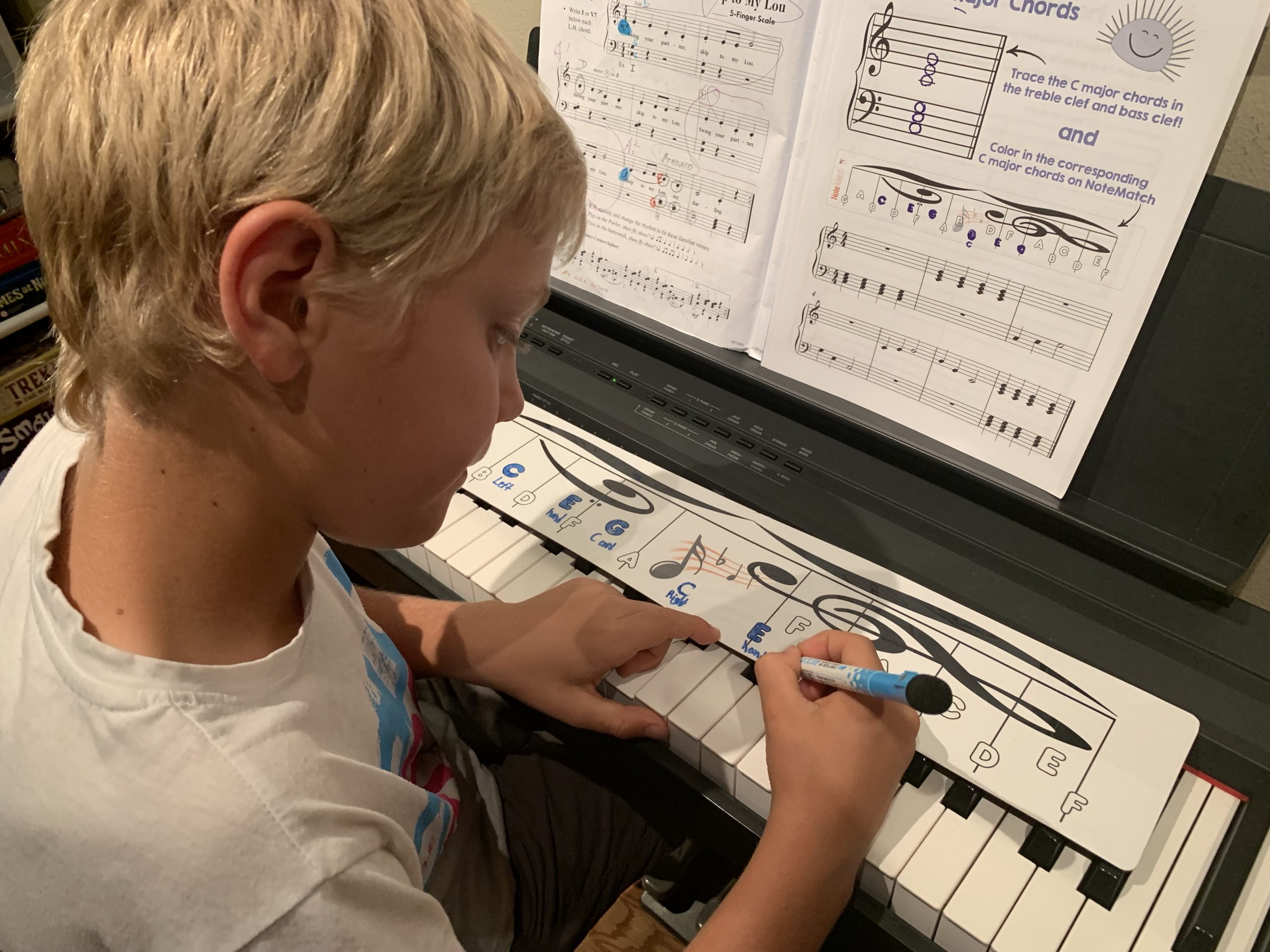 Young boy coloring in piano notes on the life-sized NoteMatch while learning about chords