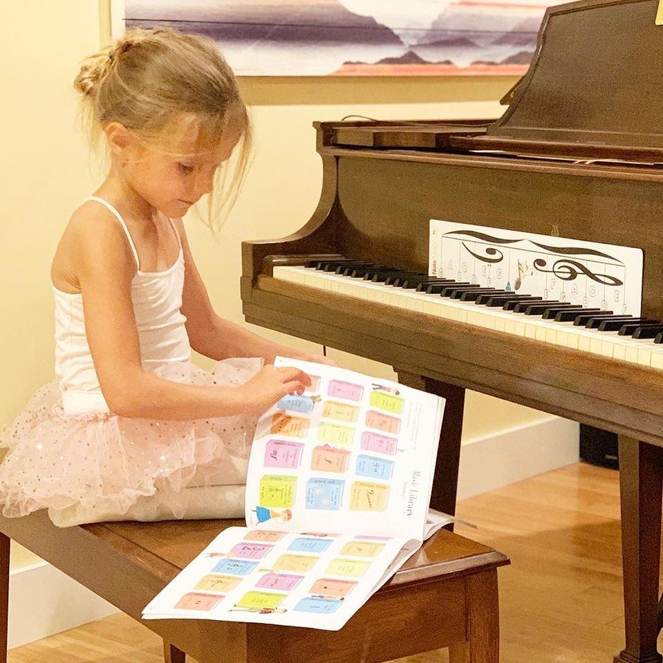 Young student flipping through the Cascade Method Piano Teacher Book