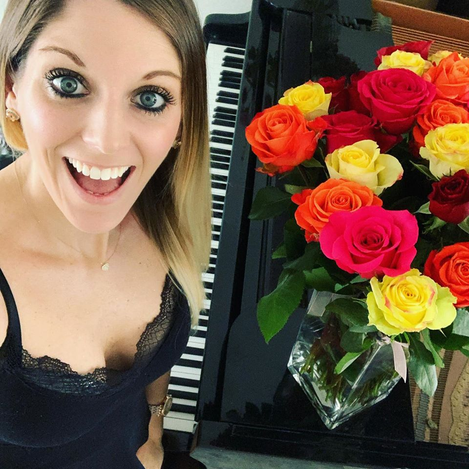 Tara Boykin posing with the piano and flowers for the teacher concert